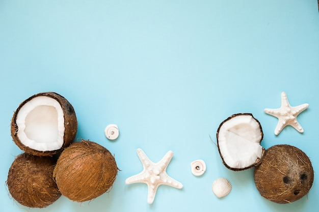 Composition avec noix de coco mûres et étoile de mer sur bleu