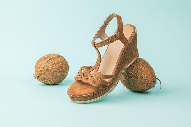 Une composition de noix de coco et une sandale de femme sur fond bleu.