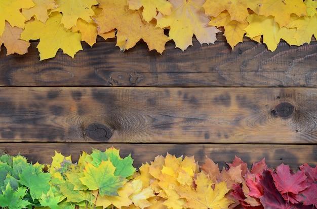 Composition de nombreuses feuilles tombées en automne jaunies sur une surface de fond en planches de bois naturelles de couleur marron foncé