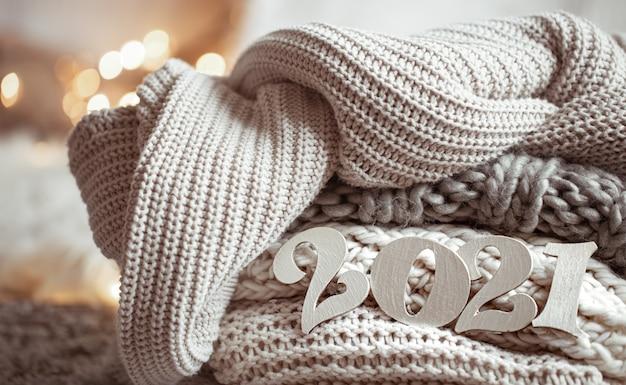 Composition de nouvel an confortable avec des numéros en bois de couleur pastel tricotés 2021 se bouchent.