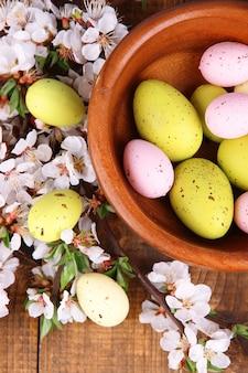 Composition avec des oeufs de pâques dans un bol en bois et des branches en fleurs, sur bois