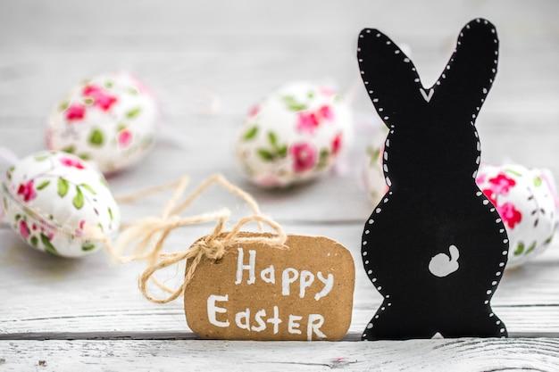 Composition d'oeufs de pâques avec du papier de lapin noir et étiquette de joyeuses pâques