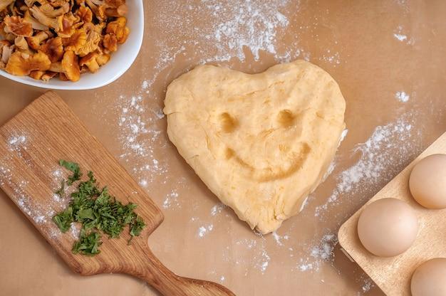 Composition d'oeufs, de pâte et de champignons sur fond beige. un ensemble de produits pour la cuisine.