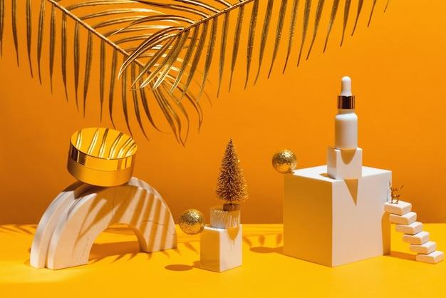 Composition d'or avec crème et sérum, formes géométriques et arbre de noël