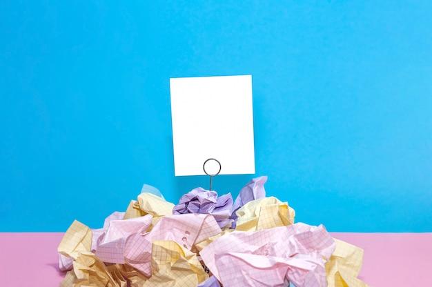 Composition de papier froissé dans les couleurs rose, jaune, bleu et violet avec carte blanche