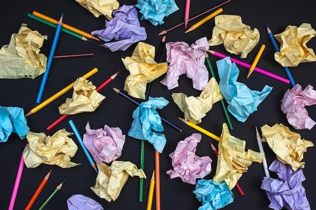 Composition de papier multicolore froissé et crayons sur une surface sombre
