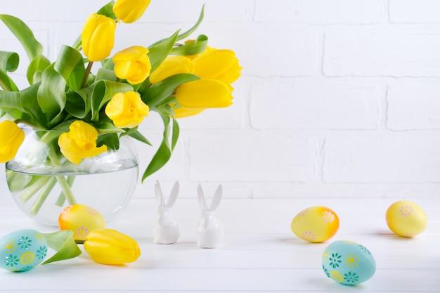 Composition de pâques avec bouquet de fleurs de tulipes jaunes dans un vase en verre et deux lapins en céramique blanche sur fond blanc
