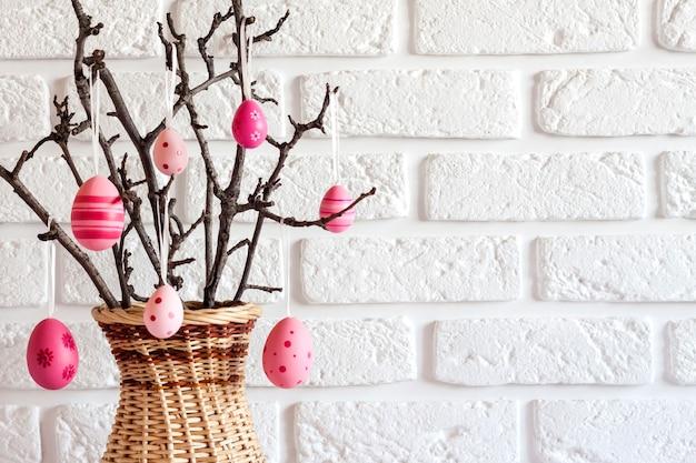 Composition de pâques avec des branches d'arbres dans un vase en osier décoré d'oeufs de couleur rose