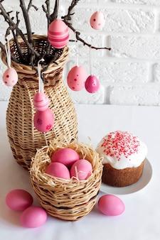 Composition de pâques avec des branches d'arbres décorées dans un vase en osier, oeufs de couleur rose dans un panier en osier et gâteau de pâques sur fond blanc. copier l'espace