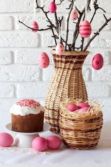 Composition de pâques avec des branches d'arbres décorées dans un vase en osier, des œufs de couleur rose dans un panier en osier et un gâteau de pâques