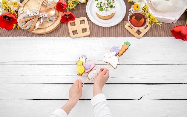 Composition de pâques avec du pain d'épice brillant sur des bâtons en mains féminines. le concept de cuisine pour les vacances de pâques.