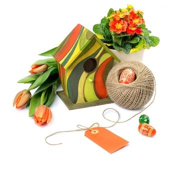 Composition de pâques avec des fleurs orange et des décorations de printemps