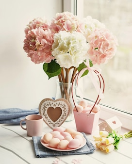 Composition de pâques avec des hortensias roses et blancs dans un vase, des tulipes jaunes et des œufs roses
