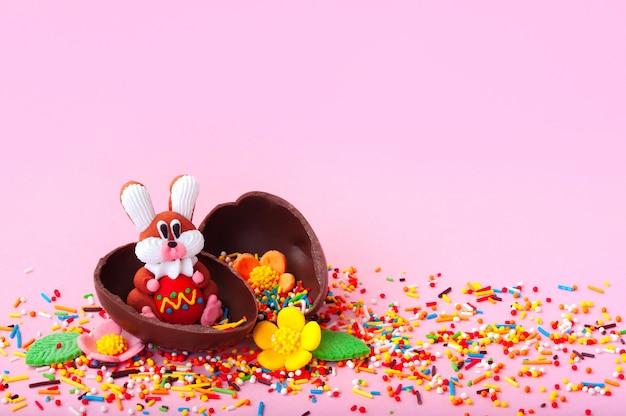 Composition de pâques avec lapin doux, fleurs et moitiés d'oeuf en chocolat sur fond rose.