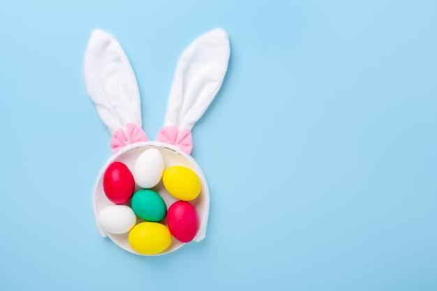 Composition de pâques mignonne. oeufs de pâques multicolores et oreilles de lapin sur fond bleu. vue de dessus. espace copie