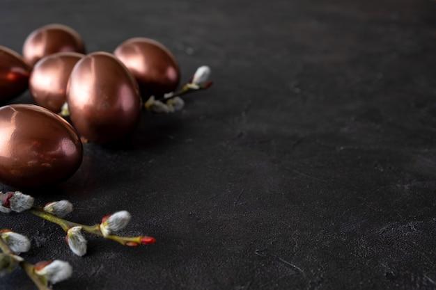 Composition de pâques avec des œufs et des brindilles de fleurs de saule. fond minimal avec des oeufs de pâques or sur fond noir. copiez l'espace.