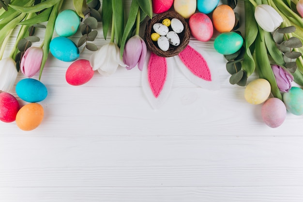 Composition de pâques avec des oeufs colorés, des oreilles de lapin, des nids et des tulipes