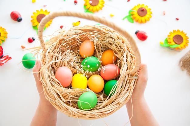 Composition de pâques d'oeufs dans le panier avec des fleurs et des bonbons sur le mur blanc