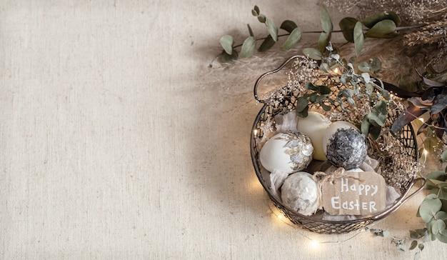 Composition de pâques avec des oeufs décoratifs dans un panier sur un espace de copie de surface légère texturée.