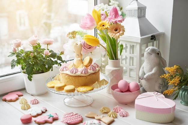 Composition de pâques avec des oeufs roses, un lapin en céramique et des fleurs dans un vase
