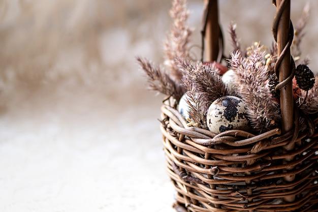 Composition de pâques avec de petits œufs et de l'herbe pelucheuse sèche dans un panier en osier.