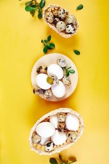Composition de pâques à plat avec des feuilles vertes et des oeufs de pâques sur fond jaune, joyeuses pâques, espace copie, vue de dessus.