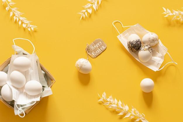 Composition de pâques de printemps avec des masques de protection et des oeufs de pâques dispersés vue de dessus.
