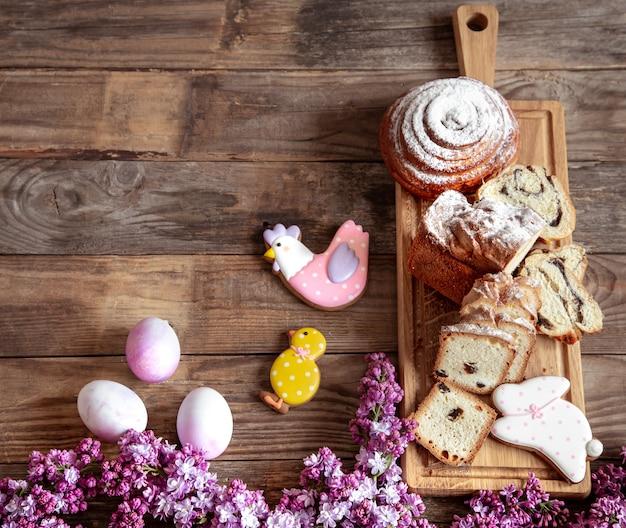 Composition de pâques avec des produits de boulangerie frais, pain d'épice, œufs et fleurs lilas sur table en bois.