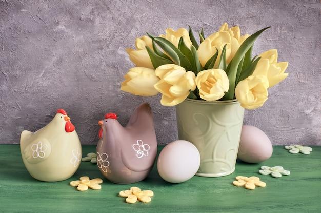 Composition de pâques avec tulipes jaunes, fleurs en feutre, poules en céramique et œufs de pâques