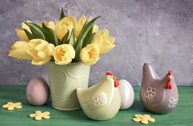 Composition de pâques avec des tulipes jaunes, des poules en céramique et des œufs de pâques