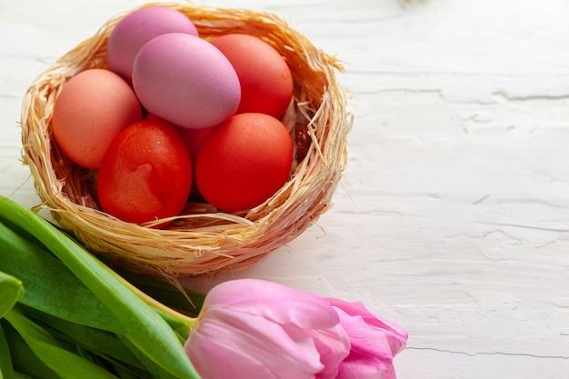 Composition de pâques avec tulipes et panier d'oeufs peints
