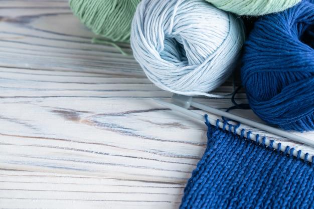 Composition de passe-temps à tricoter avec du fil bleu et vert et des aiguilles sur bois blanc