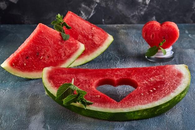 Composition avec une pastèque mûre, des feuilles de menthe et un coeur sculpté dans une tranche de melon d'eau.