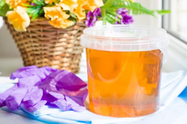 Composition de pâte de sucre en pot ou de miel de cire à épiler avec des gants violets et des fleurs