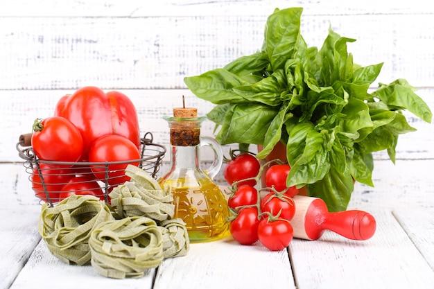 Composition de pâtes colorées, tomates fraîches, basilic, huile d'olive en bouteille sur table en bois