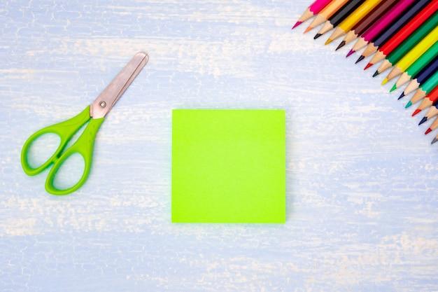 Composition pédagogique. papier vert vierge. crayons de couleur dans le coin de l'image, ciseaux avec une poignée verte au centre du cadre, fond bleu. pose à plat, vue de dessus, surface.