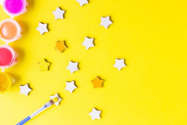 Composition avec des peintures à l'aquarelle, pinceau et forme d'étoile sur fond jaune.