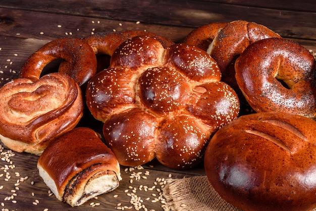 Composition de petits pains sucrés au four avec du pavot et de la confiture. cuisson sucrée présentée comme une composition sur une table en bois