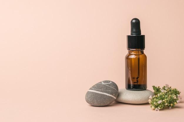 Une composition de pierres, une bouteille avec une pipette et des herbes médicinales.