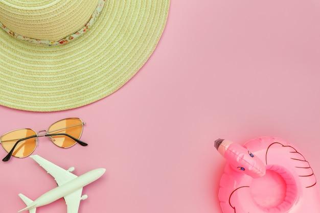 Composition de plage d'été. mise à plat simple minimale avec chapeau de lunettes de soleil d'avion et flamant gonflable isolé sur fond rose pastel. concept de voyage aventure voyage vacances. espace de copie vue de dessus.
