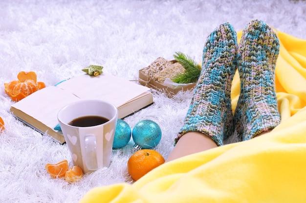 Composition avec plaid chaud, livre et jambes féminines, sur tapis de couleur