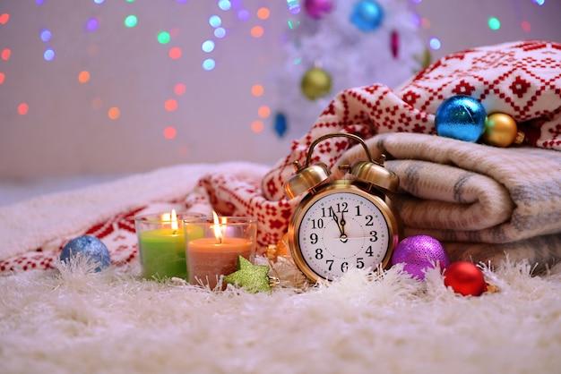 Composition avec des plaids, des bougies et des décorations de noël, sur un tapis blanc sur une surface lumineuse