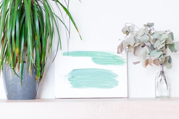 Composition de la plante verte dracaena plante d'intérieur dans un pot, plante d'eucalyptus sec dans une bouteille en verre et image abstraite peinte