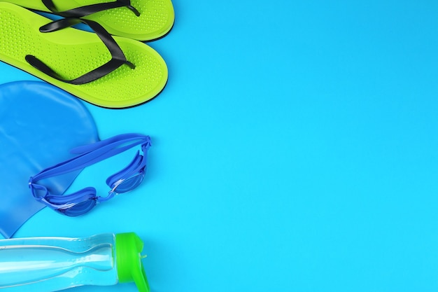 Composition à plat avec accessoires de natation sur fond bleu clair. espace pour le texte