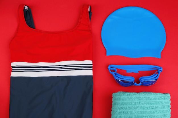 Composition à plat avec accessoires de natation sur fond rouge