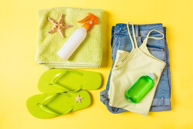 Composition à plat avec des accessoires de plage verts sur fond de couleur jaune. fond de vacances d'été. vue de dessus des articles de vacances et de voyage.