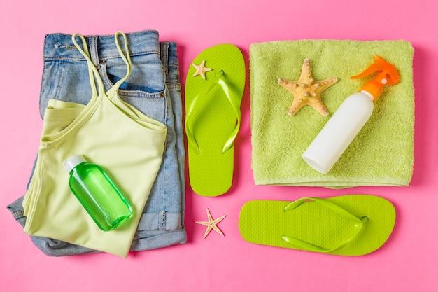 Composition à plat avec des accessoires de plage verts sur fond de couleur rose ou corail