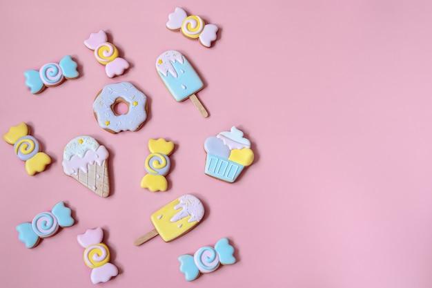 Composition à plat avec des biscuits de pain d'épice glacés brillants sur fond rose espace de copie.