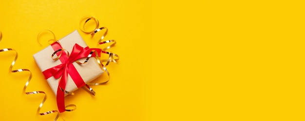 Composition à plat avec boîte-cadeau de couleur avec un arc rouge sur fond jaune