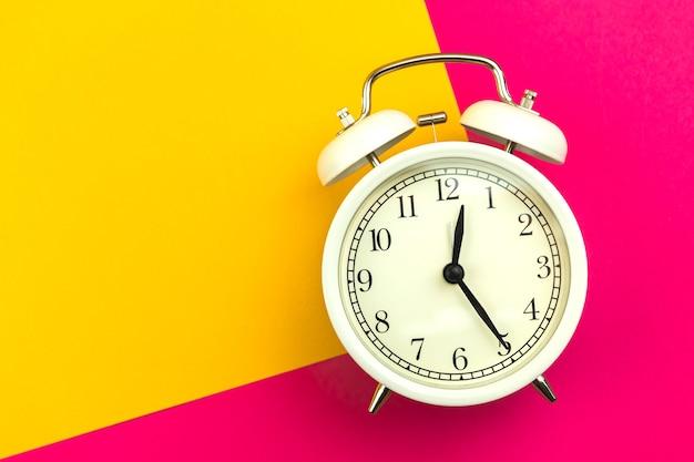 Composition à plat bonjour concept avec réveil blanc sur fond bicolore, fond coloré, photo vue de dessus